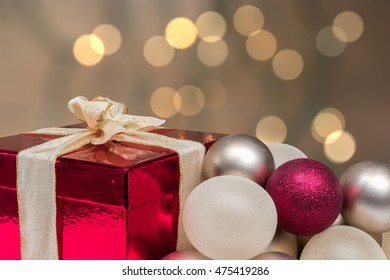 Red gift box with ribbon, baubles. Blurred  background with shining lights.