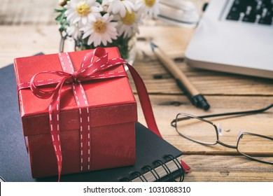Red gift box with red ribbon, blur office desk background