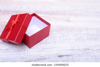 Red gift box with ribbon bow opened on vintage white wooden table