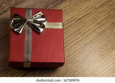 red gift box with ribbon and bow on wood