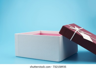 Red gift box, ribbon bundle, placed on a blue background.