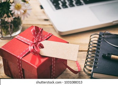 Red gift box with red ribbon and empty blank tag, blur office desk background