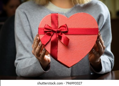 Red gift box with ribbon in the shape of heart in woman hands. For Mothers Day, Birthdays and Valentines Day