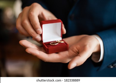 red gift box with rings in mens hands