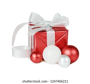 Red gift box tied with a silver ribbon with a beautiful bow and Christmas baubles isolated on a white background