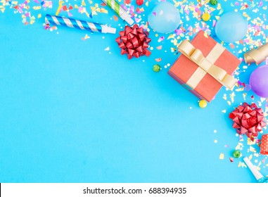 Red gift box various party confetti, balloons, on blue background with border. Flat lay. Colorful celebration pattern
