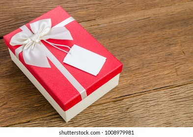 Red gift box with white bow with tag on wooden board background, valentine concept