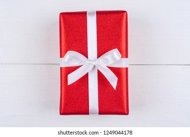 Red gift box with white ribbon bow on wooden background, copy space. Holiday greeting card. Mothers day, birthday, Women's Day, Valentine's day, Christmas, Wedding, 8March,  Easter. Top view, flat lay