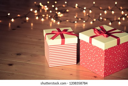 red gift boxes and christmas lights on wooden floor