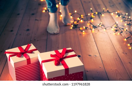 red gift boxes  feet and christmas lights on wooden floor