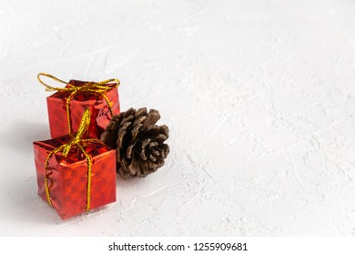 Red gift boxes with golden bows and pine cone on white textured background with copy space