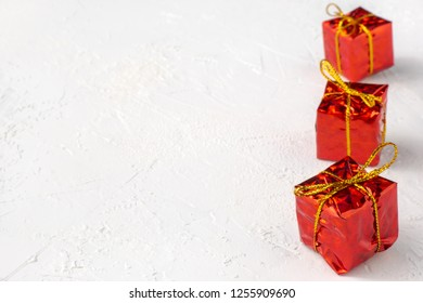 Red gift boxes in line on white textured background with copy space