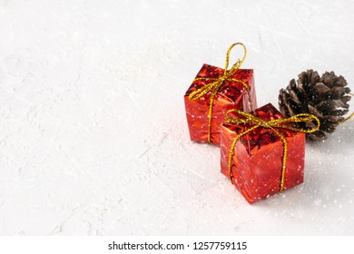 Red gift boxes and pine cone in snow on white textured background with copy space
