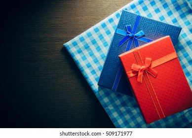 Red gift with a red ribbon and blue gift with a blue ribbon on table.