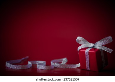 Red gift with ribbon on a red background