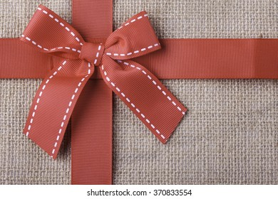 red gift ribbon on cloth background closeup