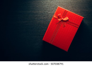 A red gift with a red ribbon on table.