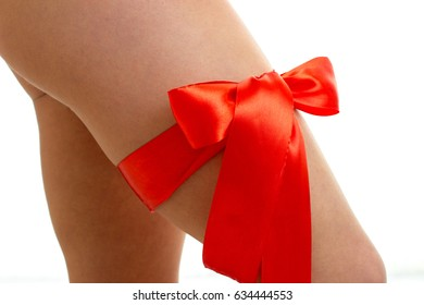 Red gift Ribbon tied on a woman's leg as Banta isolated on white background