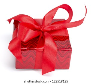 Red gift tied up by a bow on the white isolated background