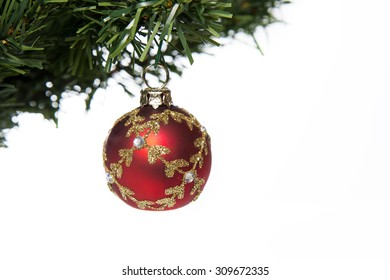 red glass ball on Christmas tree branch on white background