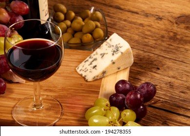 A red glass of wine and cheese