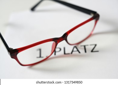 red glasses above the german text 1 Platz, that means first place, competition jury concept, selected focus, narrow depth of field