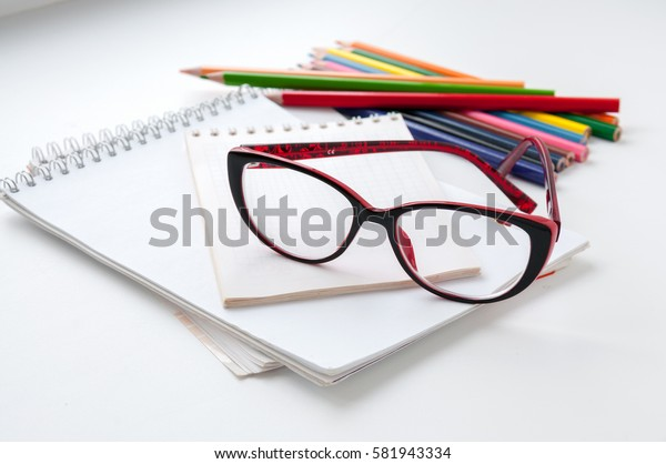 Red glasses on the notebook and colored pencils
