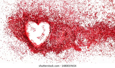 red glitter and glass shape of heart. red shiny glitter, glass heart on white background. creative concept of love, joy, happiness. close up. conceptual template for design.
