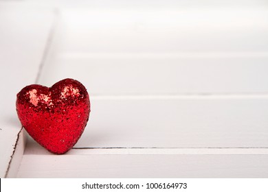 Red glitter heart on a white wooden background