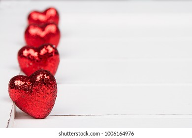 Red glitter hearts on a white wooden background