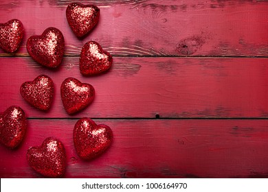 Red glitter hearts on a red wooden background