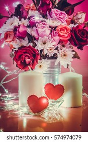Red glittering heart with lighting bulb and white candlestick. Vase of bouquet Roses in aluminium bucket on pink background. Illuminate light of love in Valentine day concept.