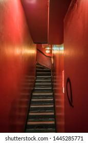 Red, gloomy seedy staircase in soho, London.