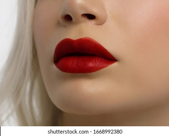 Red gloss of lips and woman's skin. The mouth is closed. Increase in lips, cosmetology. red lipstick. Open mouth and with teeth. blonde hair.