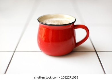 Red glossy cup with coffee or tea with milk and spices on the white table with square ornament. Masala tea