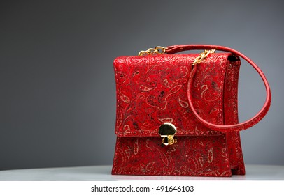 Red glossy female leather bag isolated on grey background