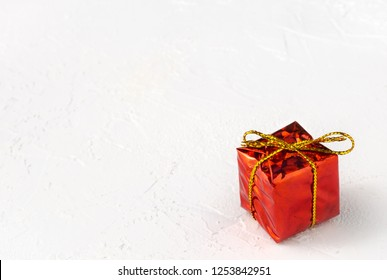 Red glossy gift box with golden bow on white textured background with copy space