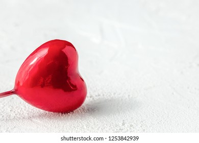 Red glossy heart on white textured background with copy space. Symbol of love and Valentine's day