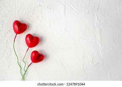 Red glossy hearts on white textured background with copy space. Symbol of love and Valentine's day