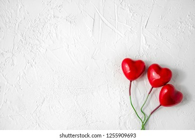 Red glossy hearts on white textured background with copy space for Valentine day