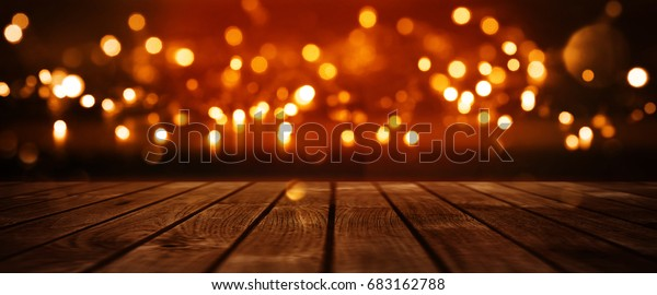 Red glowing bokeh background with empty wooden table for a solemn event