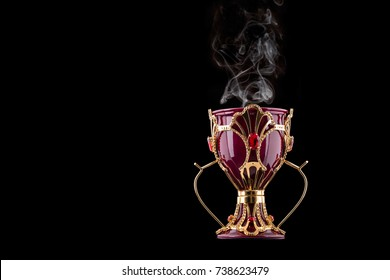 Red And Gold Arabic Traditional Incense Bukhoor Agar Wood Burner In A Mabkhara With Smoke Isolated On Black Background. Used In Majlis, Ramadan And Eid Occasions. Blank Text Space