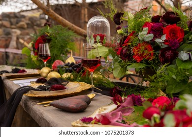 A red gold bud lying on a golden plate with a black veil, next to a glass of red wine, a wooden heart, golden fruits and flowers on an old wooden table. Decoration, gothic wedding. Copy space.