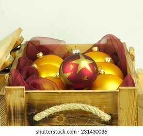 Red and gold Christmas balls encased in a stylish old wooden crate.