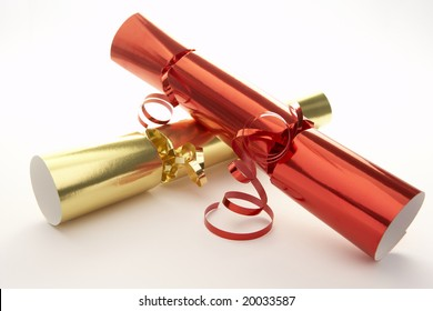 Red And Gold Christmas Crackers Against White Background