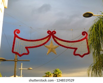 Red and gold Christmas decoration lights suspended over Andalusian village street