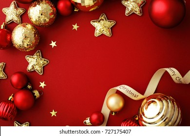 red and gold christmas ornaments, frame with copy space, red background