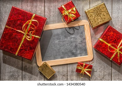 Red and gold gift boxes with over wooden background with blackboard