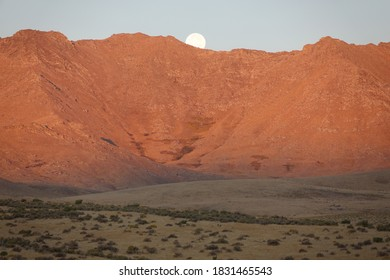 Red and gold mountain in morning sun with moonset on the mountaintop