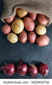 Red and Gold potatoes in hessian sack with red onions on slate table top with copy space - vertical portrait format